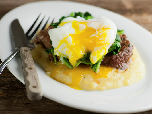 Steak and eggs on polenta
