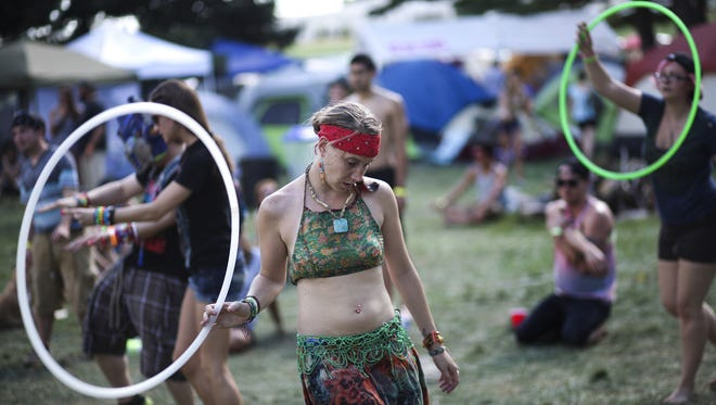 Hula hoopers dance to the music during MojoStock 2013 at Sleepybear Campground in Noblesville, Ind.