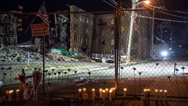 Crosses, flags, flower stems and lit candles adorn a chainlink fence separating the Walnut Street neighborhood from the old Weaver Organ and Piano building Friday, March 23, 2018, after a neighborhood-organized vigil for Ivan Flanscha and Zachary Anthony, two York City firefighters who died in a building collapse nearby on Thursday. Assistant chief Greg Altland and firefighter Erik Swanson sustained injuries in the same collapse.