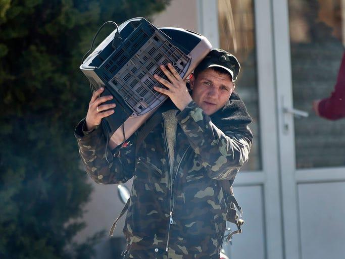 A Ukrainian airman carries a television set as he leaves Belbek air base on March 21 outside Sevastopol, Crimea.