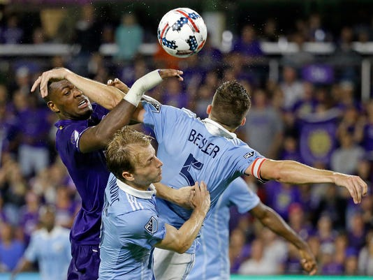 Orlando City's Cyle Larin, left, tries to head the ball to the goal as Sporting Kansas City's Matt Besler (5) and and Seth Sinovic, center, defend during the second half of an MLS soccer match, Saturday, May 13, 2017, in Orlando, Fla. The game ended in a 2-2 draw. (AP Photo/John Raoux)
