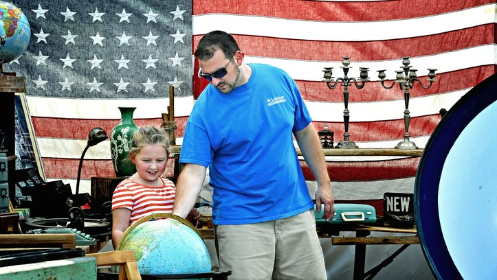 Greg Tisdale shows his daughter Graceland the world (actually a globe) at the Nashville Flea Market.With more than 900 vendors, Nashville Flea Market continues to grow. Market director Deborah Dornan says they have had to turn away vendors this year because they don't have the room. Saturday July 25, 2015, in Nashville, Tenn.
