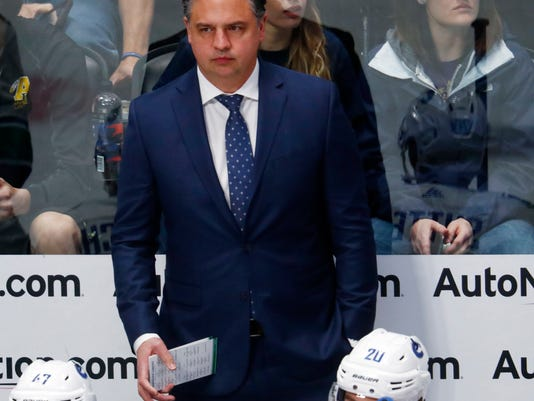 Vancouver Canucks head coach Travis Green looks on from the bench against the Colorado Avalanche in the first period of an NHL hockey game Monday, Feb. 26, 2018, in Denver. (AP Photo/David Zalubowski)