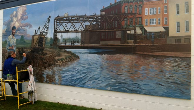 Artist Stacey Kirby putting the final touches on the new Erie Canal mural on the DPW Building in Brockport.