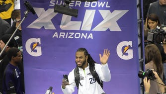 Seahawks cornerback Richard Sherman waves to members of the press during media day for Super Bowl XLIX.