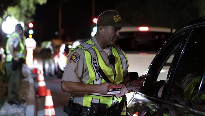 Authorities screen vehicles during a DUI and driver's license checkpoint.