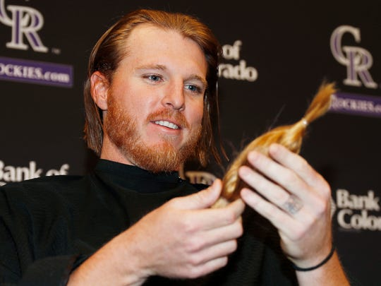 Colorado Rockies starting pitcher Jon Gray admires the eight-inch ponytail cut from his long locks as Gray donates his hair to Locks For Love, a non-profit organization that provides hairpieces to financially disadvantaged children on Tuesday, April 11, 2017, in Denver. Gray has not cut his hair for more than two years before Tuesday's trim. (AP Photo/David Zalubowski)