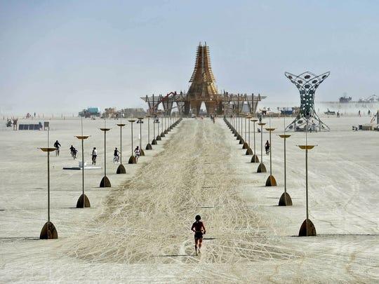 Burning Man 2017 A burner runs toward The Temple at Burning Man.