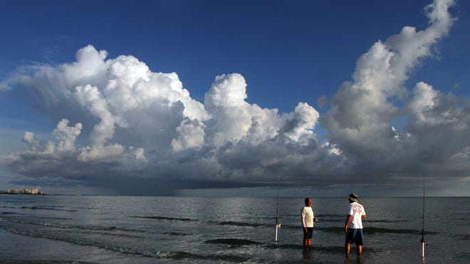 Beachgoers fish in the Gulf of Mexico on Thursday on Fort Myers Beach. Southwest Florida's wet season begins today, and the region has already had a few afternoons of rain.