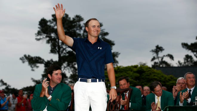 Jordan Spieth (middle) waves to the crowd during the green jacket ceremony as 2014 champion Bubba Watson looks on after The Masters golf tournament at Augusta National Golf Club.