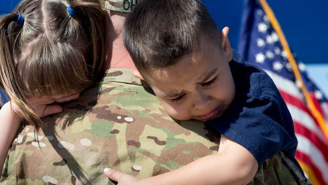 U.S. Army Combat Medic Nate Ohlney (center) hugs his children, Joshua and Makayla, during a surprise homecoming in 2013 at MacArthur Elementary School in Mesa.