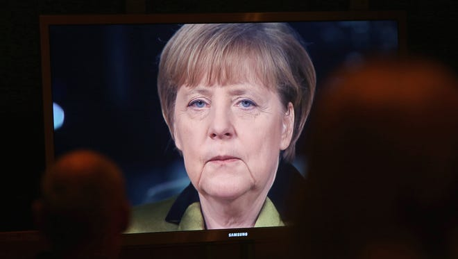 German Chancellor Angela Merkel is seen speaking on a video monitor as she gives her New Year's television address to the nation at the federal chancellery on Dec. 30, 2013 in Berlin.