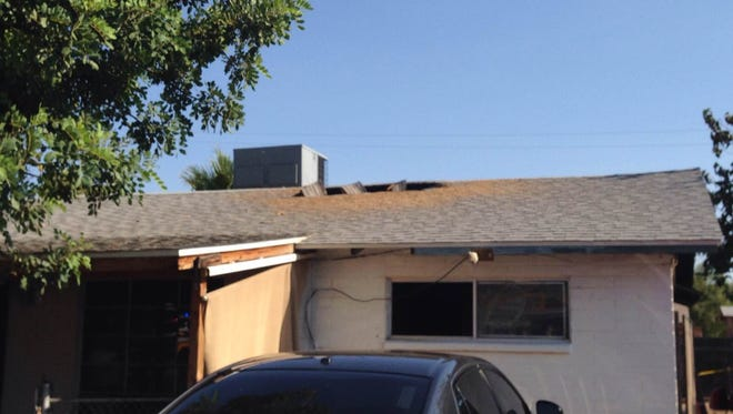Glendale firefighters opened up the roof of this home to help contain flames on Thursday, Aug. 20, 2015.