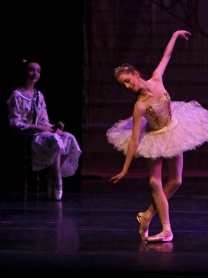 """Princess Aurora (Jenna Holcomb) performs during Sleeping Beauty's story of """"Once Upon a Ballet"""" as Mae (Zoe Knight-Stockton) looks on Friday afternoon at Memorial Auditorium."""