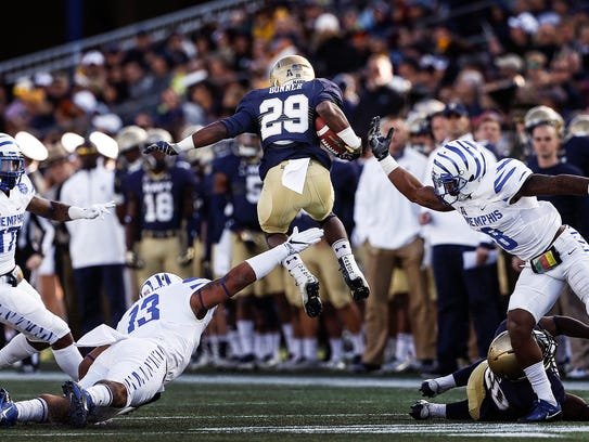 Navy running back Darryl Bonner (middle) leaps over