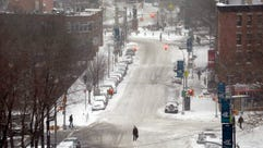 A pedestrian crosses an empty snow-covered street on