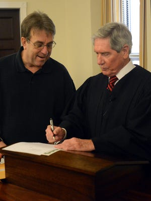 Chancellor James Butler (right) signs Madison County Commissioner Doug Stephenson's oath at the conclusion of a swearing-in ceremony Thursday.