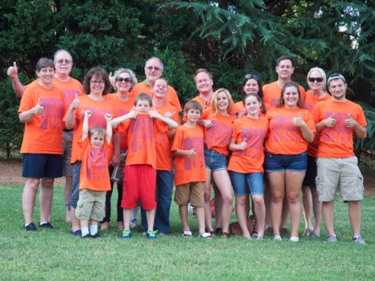 The Smith family wears purple and orange shirts, designed