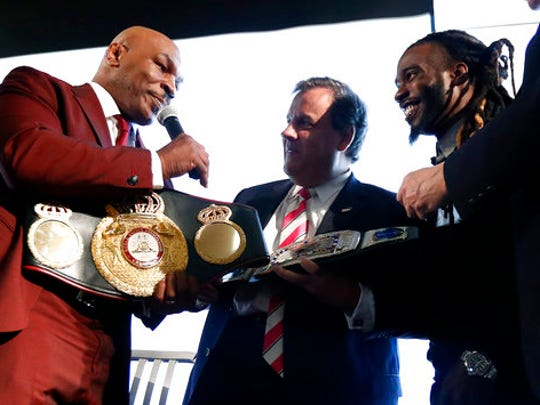 New Jersey Gov. Chris Christie, center, is presented with a belt by boxer Mike Tyson, left, for Christie's work in promoting help for ex-prisoners re-entering society, during the 4th Annual New Jersey Prisoner Reentry Conference, Thursday, April 13, 2017, in Jersey City, N.J.
