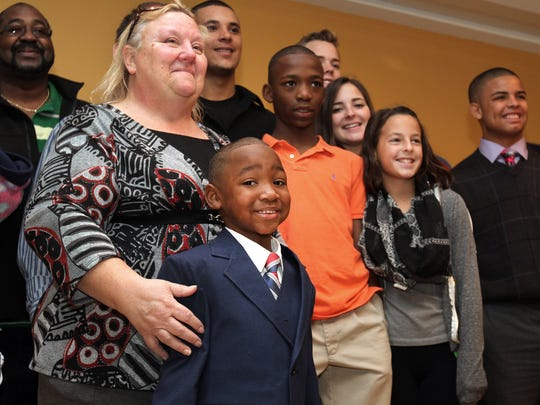 In this 2014 photo, Janet Hans keeps her 4-year-old son, Naeim, close by as they take photographs with their extended family during a reception at the Ocean County Library in Toms River, Friday, after his adoption was finalized at the courthouse.