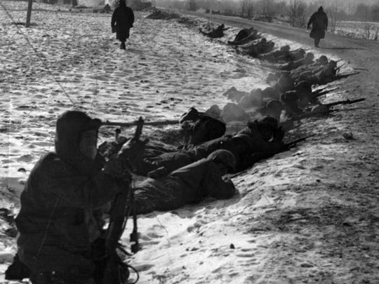 A detail of U.S. Marines lies in the snow with rifles ready at a curve in the road near the Chosin Reservoir, North Korea, Nov. 29, 1950. The First Marine Division fought here for 14 days in minus-30 degree temperatures against 120,000 Chinese in one of the most savage battles of the Korean War.