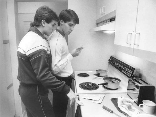 Steve Yzerman and Lane Lambert, who are both on the Detroit Red Wings' hockey team and room together in the Riverfront apartment complex in Detroit, Mich. (next to Joe Louis Arena), look at a Halloween photo while they cook hot dogs and macaroni and cheese for their lunch.