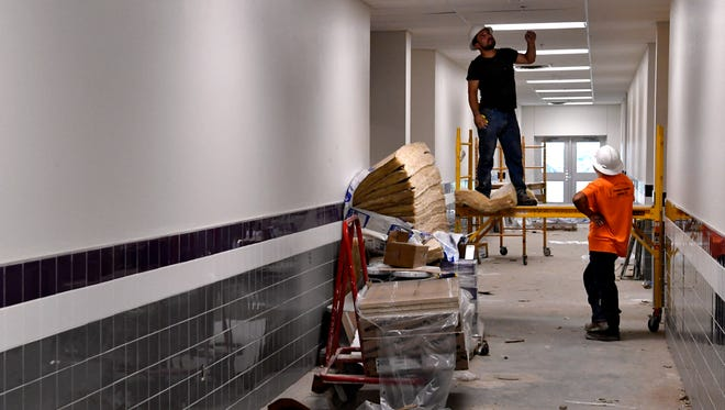 Men work in one of the hallways of Wylie East Elementary School Friday. The new school is scheduled to be ready for the fall.