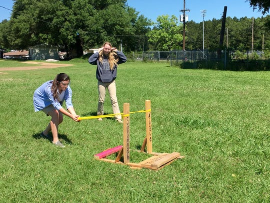 Savannah Pogue and Nicole Mann test their slingshot Wednesday. It launched a ball 212 feet and won them the pizza prize.