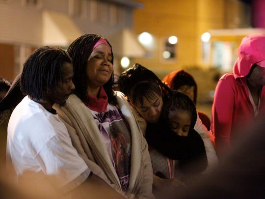 Marie Hughes Clark, center, is comforted by her husband Deon Clark, left; her sister, Jennifer Gaskin; and granddaughter Jayla Kidd, 10, during a vigil Jan. 9, 2014, for Hughes' three grandchildren who were killed in a Jan. 4 fire in New Albany, Ind.