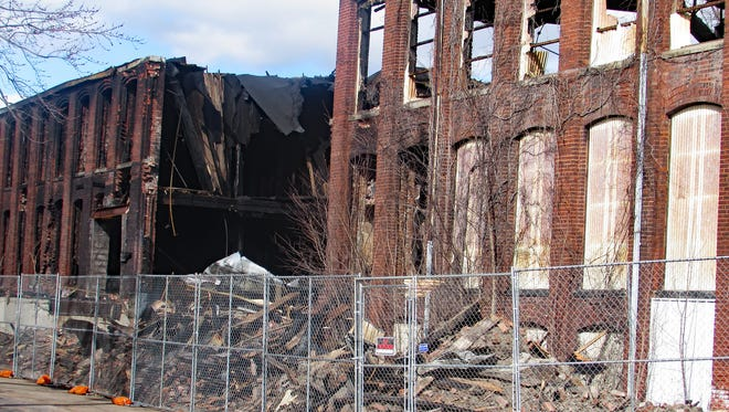 A security fence was erected earlier this week around a burned-out warehouse building on Prescott Avenue in Elmira Heights.