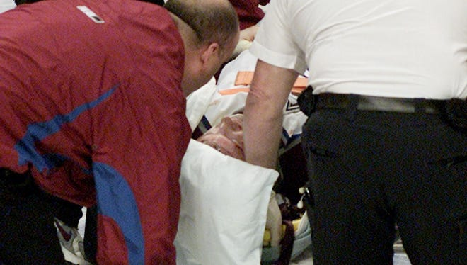 Colorado Avalanche forward Steve Moore is taken away by medical staff after sustaining an injury from Vancouver Canucks' Todd Bertuzzi.