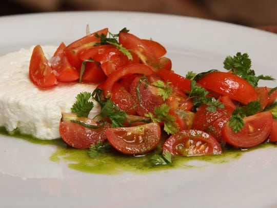 Housemade ricotta salata, grape tomato bruschetta, basil oil and chervil at Porta.