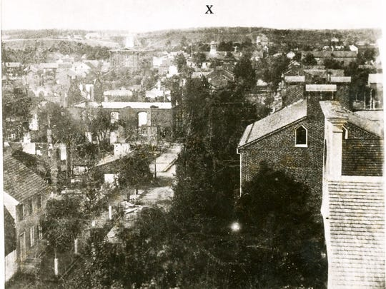 "A photograph of Chambersburg looking north from the Market House towards North Second and East King streets after the Burning of Chambersburg on July 30,1864. The cupola of the old jail is below the ""X."""
