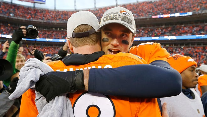 Denver Broncos quarterback Peyton Manning is congratulated by quarterback Brock Osweiler, right, following the AFC Championship game between the Denver Broncos and the New England Patriots.