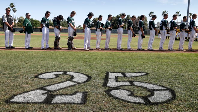 Flagstaff High School players observe a moment of silence for Evan Wissen (#25), May 2, 2017, before the start of their state baseball playoff game against Marcos de Niza High School, 6000 S. Lakeshore Drive, Tempe. Evan died suddenly and unexpectedly on April 27th.