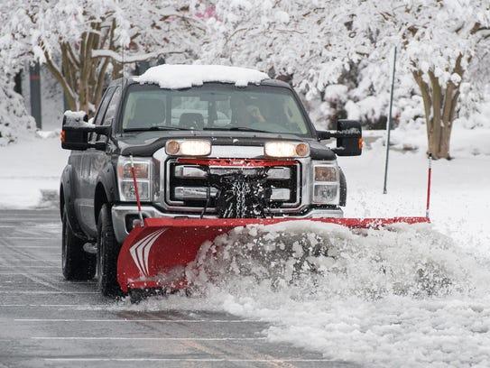 A plow truck clears a parking lot along East Market