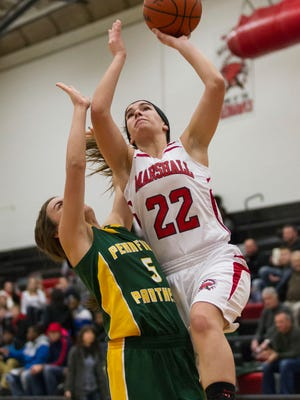 Jill Konkle of Marshall gets up a shot over Jessica Roan of Pennfield in girls' basketball action on Friday.