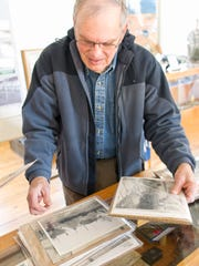 John Anderson sorts through old photographs involving National Guard soldiers from Michigan.