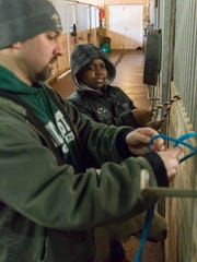 Dominick Edwards learns from Brett Linsley the proper way to tie off a horse at Binder Park Zoo.