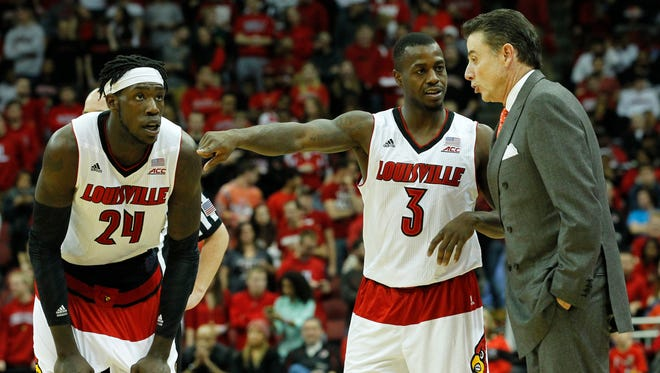 University of Louisville head coach Rick Pitino (R) talks with Chris Jones (3) and Montrezl Harrell (24) during play against Savannah State during the second half of play at the KFC Yum! Center in Louisville, Kentucky, November 24, 2014.
