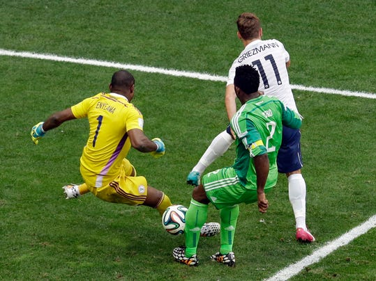 Nigeria's Joseph Yobo, front, scores an own goal to give France a 2-0 lead during the World Cup round of 16 soccer match between France and Nigeria at the Estadio Nacional in Brasilia, Brazil, Monday, June 30, 2014. (AP Photo/Hassan Ammar)