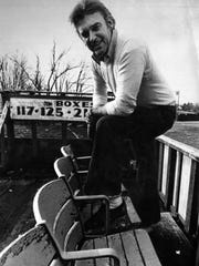 "Larry Luebbers poses in the ""grandstand"" area of his backyard stadium in Union, Kentucky."