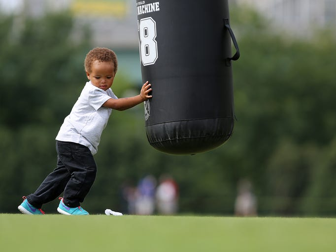 A young fan works out during training camp on the practice field at Paul Brown stadium on Monday.