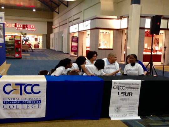Students, faculty and staff of Central Louisiana Technical Community College discuss how they will answer a black history question in a quiz bowl competition against Louisiana State University of Alexandria at the Alexandria Mall on Thursday.