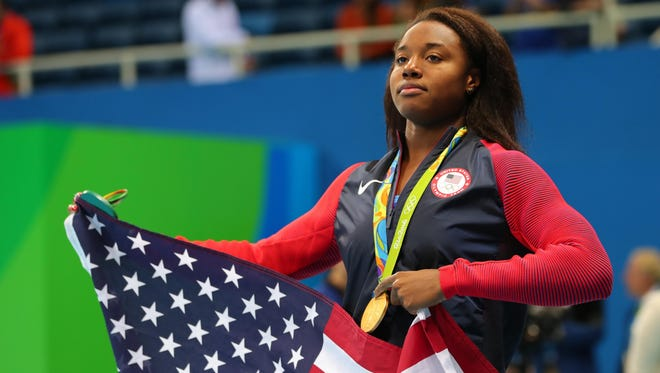 Simone Manuel (USA) with an American flag after the women's 100m freestyle final in the Rio 2016 Summer Olympic Games at Olympic Aquatics Stadium.