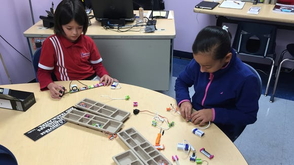 Harmony Science Academy fourth-graders Samantha C., left, and Amy H. show off their work with Little Bits electronics kits.