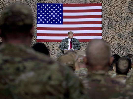 President Donald Trump speaks to members of the military at a hangar rally at Al Asad Air Base, Iraq, Wednesday, Dec. 26, 2018. President Donald Trump tells troops serving in Iraq that he got them their first pay raise in 10 years and it's a big one. No, and not exactly. (AP Photo/Andrew Harnik)