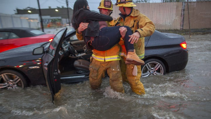A firefighter carries a woman from her car after it was caught in street flood as a powerful storm moves across Southern California.