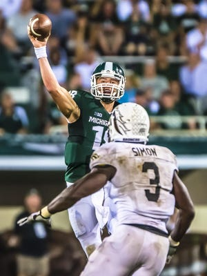 MSU quarterback Connor Cook (top) passes while under pressure from Johnnie Simon of Western Michigan during their game Friday August 30, 2013 in East Lansing. KEVIN W. FOWLER PHOTO