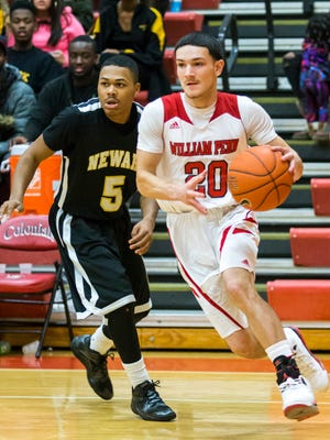 William Penn's Daniel Walsh (20) drives past Newark's Shannon McCants on Jan. 7. The Colonials moved up to No. 2 in The News Journal's boys basketball rankings this week.
